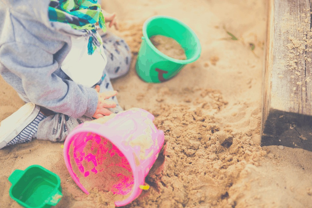child playing in a sandbox