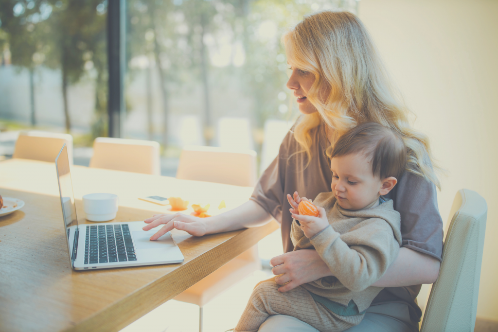 mom working while holding child