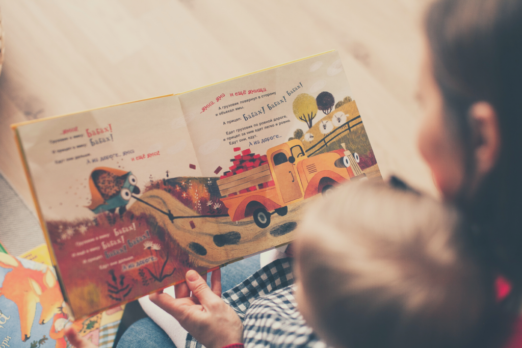 mom reading story book to toddler