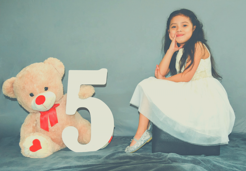 girl sitting next to toy bear