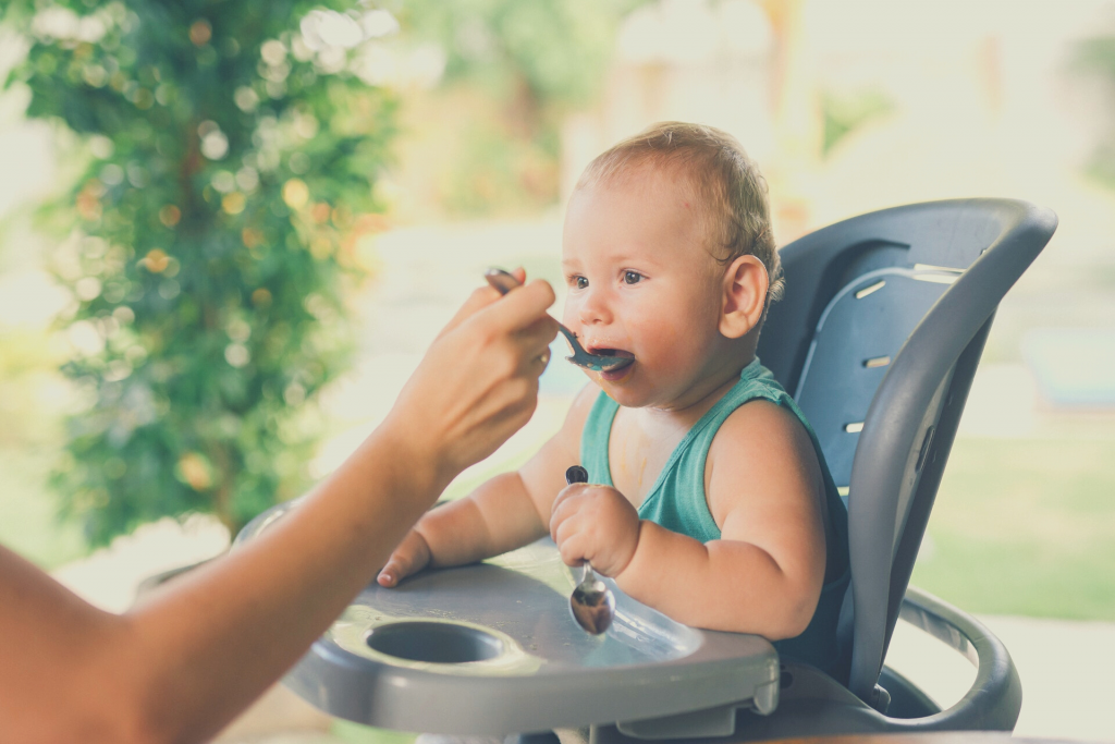 baby feeding baby with spoon