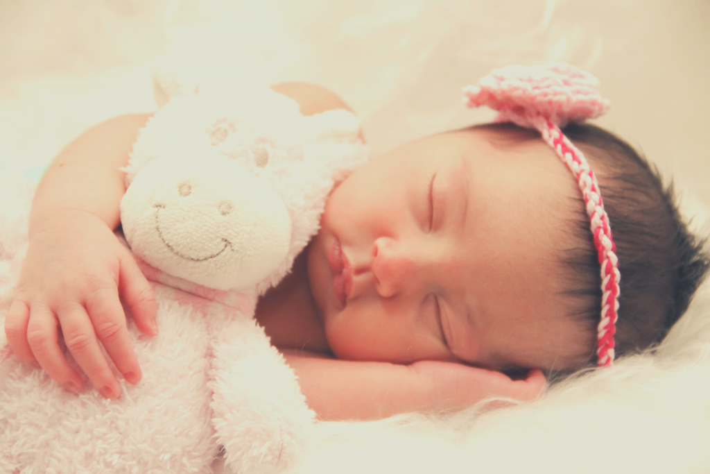 baby sleeping with plush toy