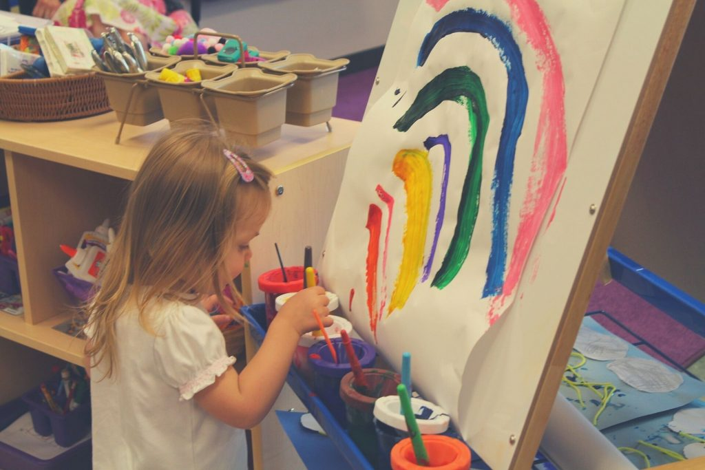 kid painting a rainbow