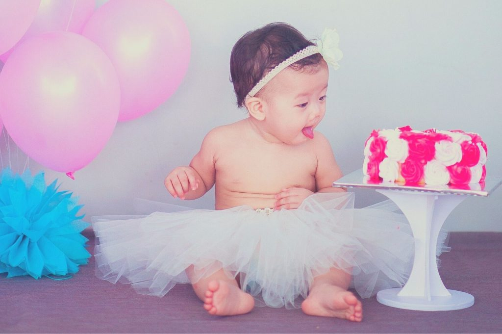 baby girl looking at a cake