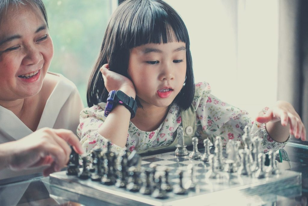 girl playing chess with grandmother
