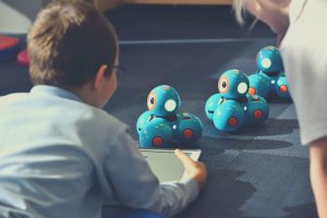 kid controlling robots with tablet
