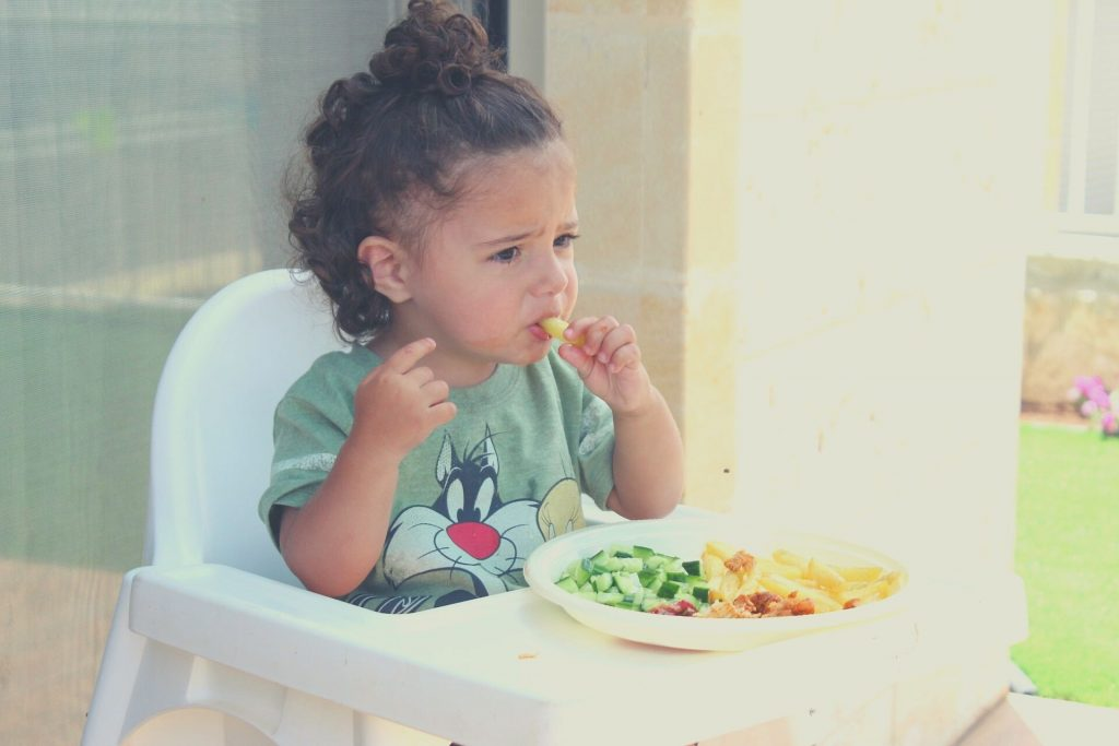 kid eating on booster seat