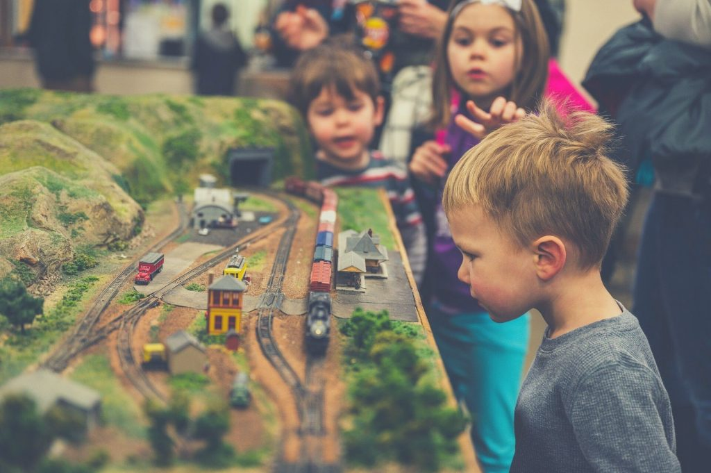 kid looking at toy train table